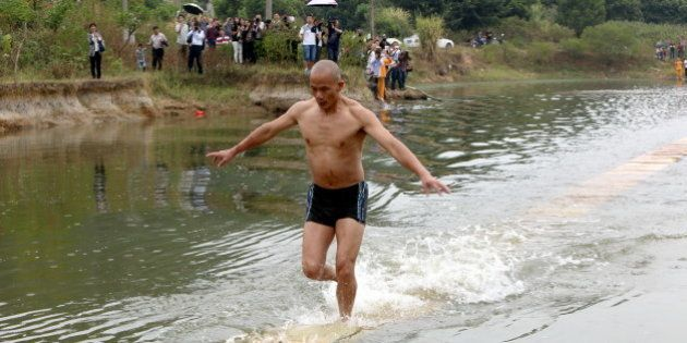 QUANZHOU, CHINA - OCTOBER 26: (CHINA OUT) Shi Liliang, a monk of Shaolin Temple, runs on plywoods which...