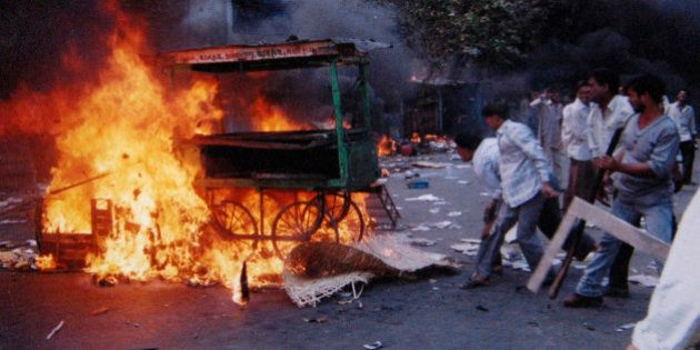 ** FILE ** A mob sets fire to vehicles and other goods in the Khokhara area in Ahmadabad, India, in this...