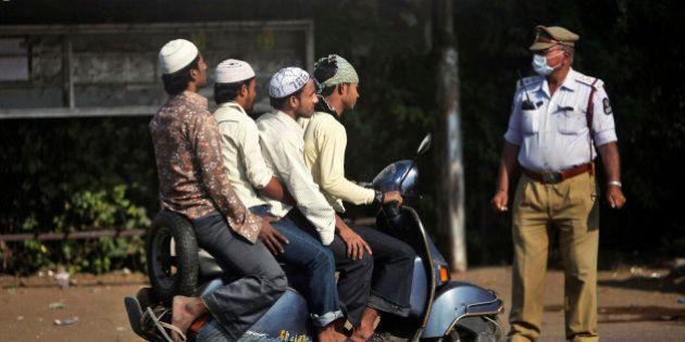 An Indian police officer controls traffic as Muslim men arrive in a scooter to offer prayers on Eid al-Adha...