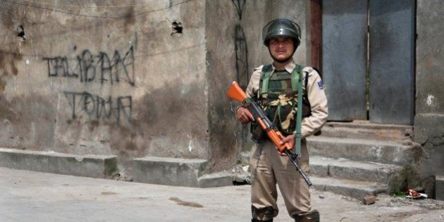 An Indian paramilitary soldier stands guard on a street during curfew in Srinagar, India, Friday, May...