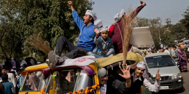 Supporters of the Aam Aadmi Party, or Common Man's Party, shout slogans as they sit on an autorickshaw...