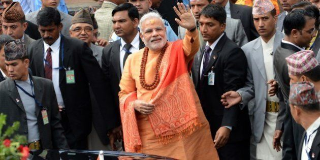 Indian Prime Minister Narendra Modi (C) waves to well-wishers as he leaves following his visit at the...