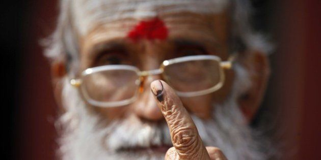 NEW DELHI, INDIA - FEBRUARY 7: A saint showing his inked finger after casting his vote during the Delhi...