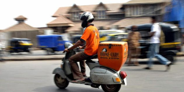 TO GO WITH LIFESTYLE-INDIA-ANIMALS-FOOD,FEATURE BY PHIL HAZLEWOOD A Home-Care Dog Food delivery boy rides...