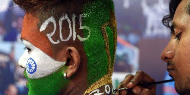 An Indian cricket enthusiast gets his face painted in the colours of his national flag at a salon offering...