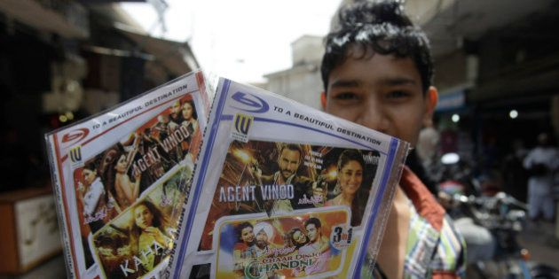 A Pakistani boy shows CDs of Indian film Agent Vinod he bought from a store in Karachi, Pakistan on Monday,...