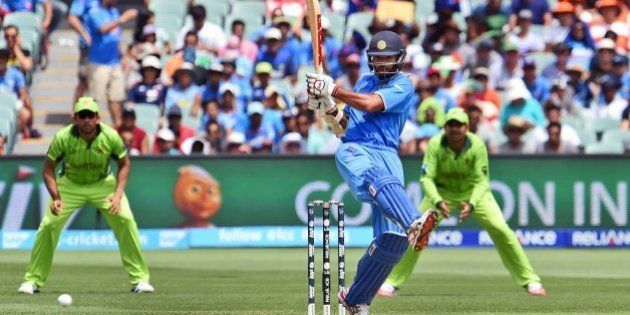 Indian batsman Shikhar Dhawan (C) pulls a ball towards the boundary from the Pakistan bowling in their...