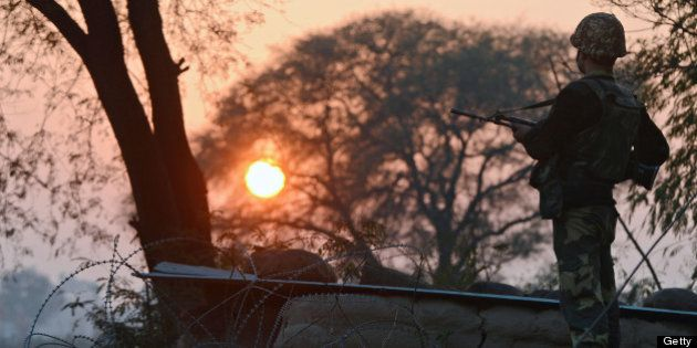 An Indian Border Security Force (BSF) soldier keeps watch at an outpost along the India-Pakistan border...