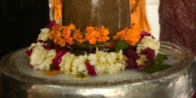 Indian Hindu devotees pour milk over a Shivling or idol of Lord Shiva at a temple in Amritsar on March...