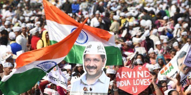 Supporters of the Aam Aadmi Party (AAP) watch leader Arvind Kejriwal being sworn in as Delhi chief minister...