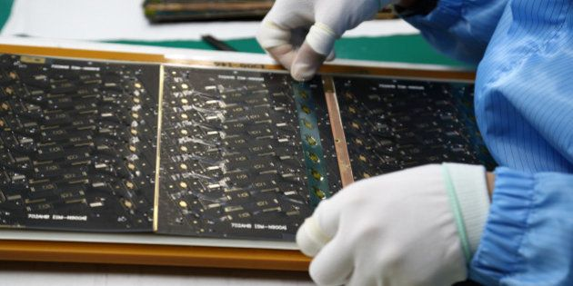 An employee attaches protective film to a Flexible Printed Circuit Board (F-PCB) panel on the production...