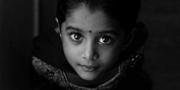 Indian girl Child in traditional dress looking up. Black and white shot. Window