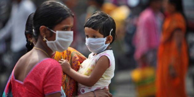 An Indian woman and a child cover themselves with protective masks after the news of the outbreak of...