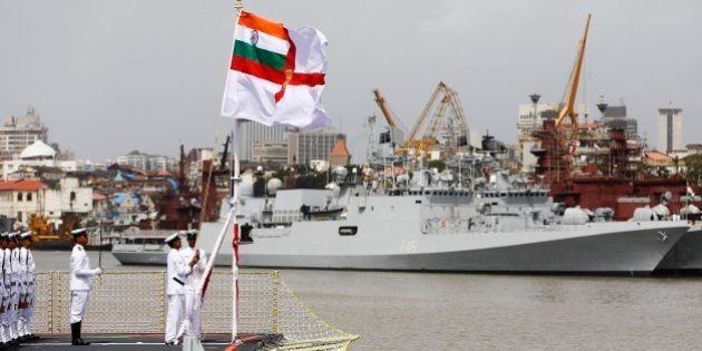 Indian naval officers hoists the navy flag during a ceremony to induct the largest indigenously built...