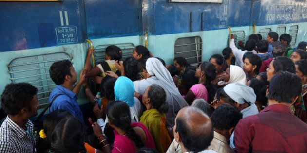 Indian women stand in front of a train door that was closed by a security officer asking them to first...