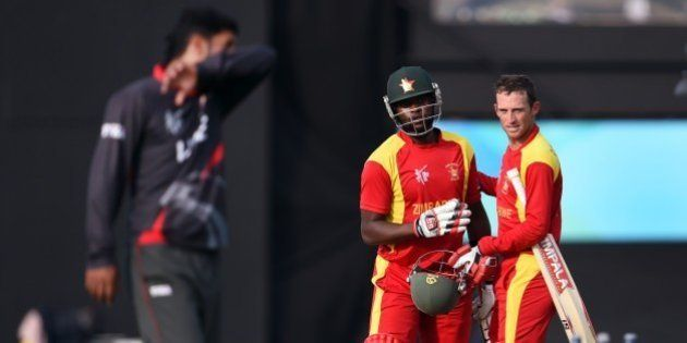Zimbabwe batsmen Sean Williams (R) and Elton Chigumbura (2nd L) celebrate victory as United Arab Emirates...