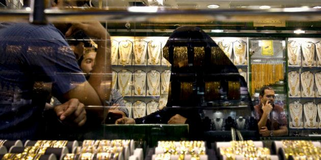 In this Thursday Oct. 11, 2012 photo, an Emirati woman discusses her purchases with a salesman at a jewelry...