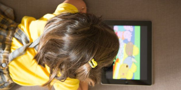 Girl watching cartoons online with the iPad tablet laying in the sofa at home with view from