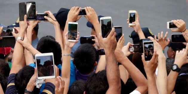 In this Friday, Jan. 16, 2015, photo, Filipino Catholics prepare to take photos, using their mobile phones...