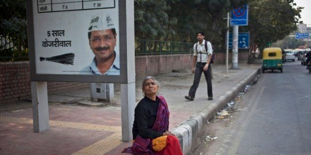 An Indian woman waits for bus as she sits near an election advertisement with a photograph of Aam Aadmi...