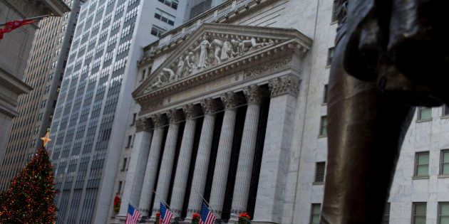 Pedestrians walk past the New York Stock Exchange (NYSE) in New York, U.S., on Friday, Jan. 2, 2015....