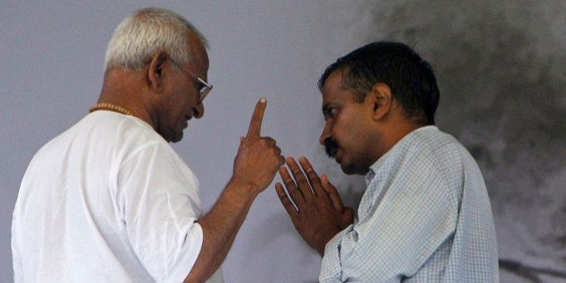India's anti-corruption activist Anna Hazare, left, speaks with supporter Arvind Kejriwal on the 8th...