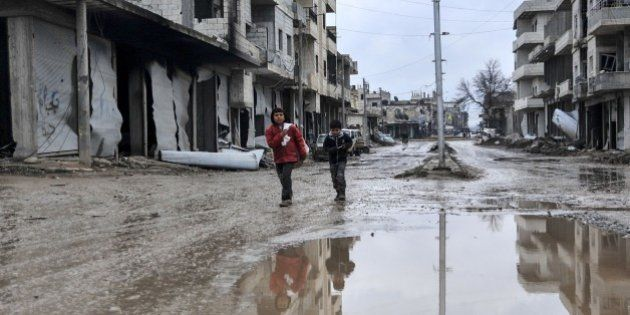 ALEPPO, SYRIA - FEBRUARY 18: Kids walking among the destroyed buildings of the Syrian town of Kobani...