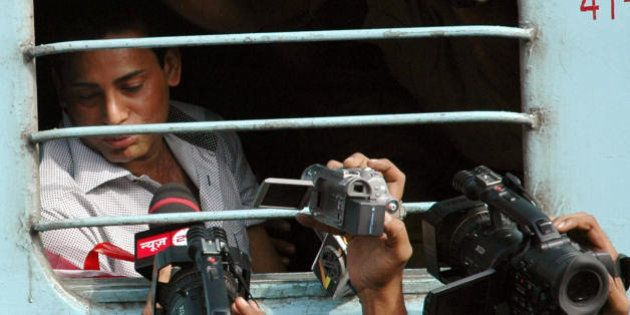 Indian under world don Abu Salem talks to media representatives as he sits in a train leaving to Mumbai,...