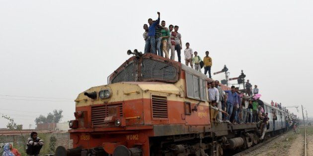 Indian passengers stand and hang onto a train as it departs from a station on the outskirts of New Delhi...