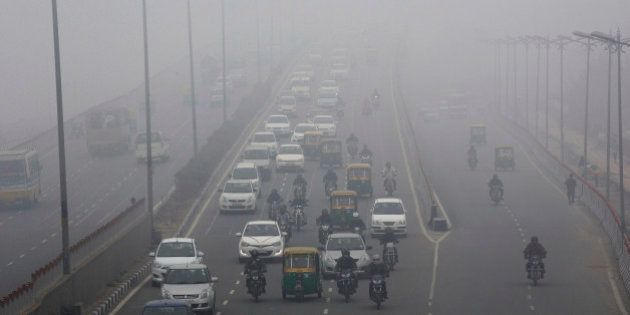 Traffic moves along a road shrouded in haze in New Delhi, India, on Monday, Jan. 20, 2014. India, China...