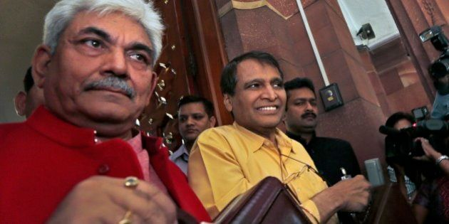 Indian Railway Minister Suresh Prabhu, centre, and junior Railway Minister Manoj Sinha, left, lifts the...