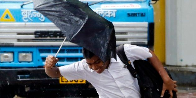 An Indian school boy jumps over a puddle of water as it rains in Mumbai, India, Wednesday, July 2, 2014....