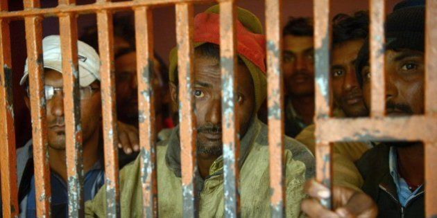 Arrested Indian fishermen stand in a police lockup in the port city of Karachi on January 22, 2015. Pakistani...