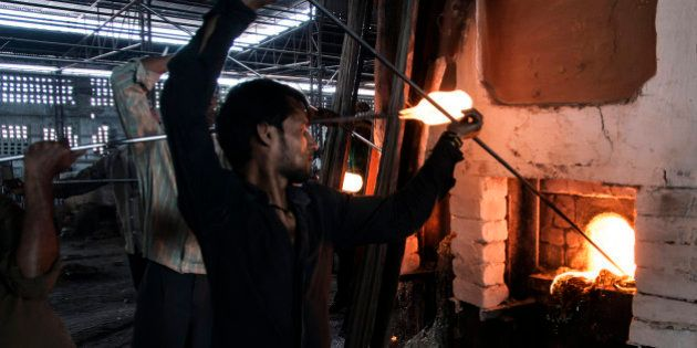 Glassmiths use punties to gather molten glass from the furnace at the Kohinoor Bangle Industries factory...