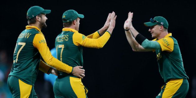 South Africa's AB De Villiers is congratulated by teammates Dale Steyn, right, and Rilee Rossouw, left,...