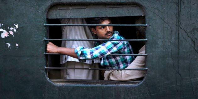 An Indian passenger sits on the lap of another man as he travels in a crowded local train on the outskirts...