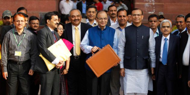 Indian Finance Minister Arun Jaitley, center in blue jacket, display a briefcase containing union budget...