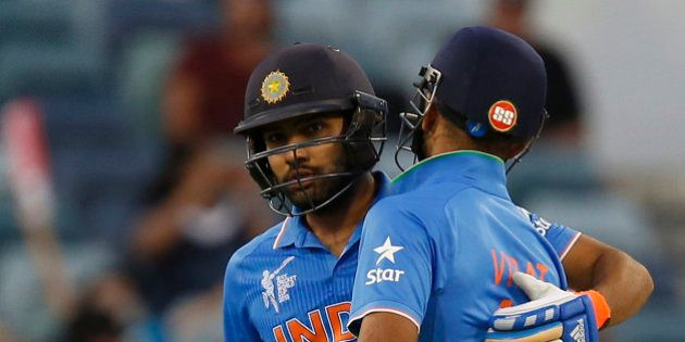 India's Virat Kohli right congratulates Rohit Sharma after he hit a half century during their Cricket...
