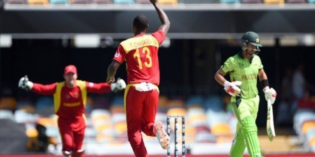 Zimbabwe bowler Tendai Chatara (C) celebrates after taking the wicket of Pakistan cricketer Ahmed Shehzad...