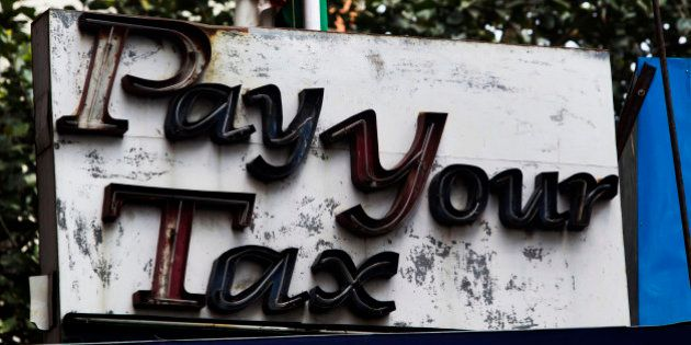 A sign reading 'Pay Your Tax' sits outside the income tax office in Kolkata, India, on Monday, March...