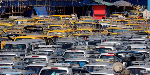 In this Tuesday, March 25, 2014 photo, traditional black-and-yellow licensed cabs and private cabs stand...