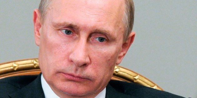 Russian President Vladimir Putin, listens during a meeting at the Novo-Ogaryovo residence outside Moscow,...