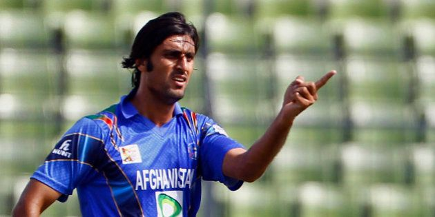 Afghanistan's Shapoor Zadran celebrates after taking the wicket of Sri Lanka's Lahiru Thirimanne...