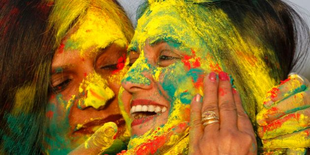 Indian women smear colors on their faces as they