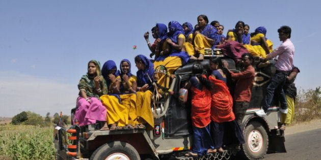 ALIRAJPUR, INDIA - MARCH 2: Young tribal women travelling on a overloaded jeep to go to the Bhagoria...