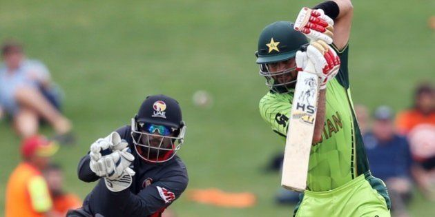 Pakistan's Ahmed Shehzad (R) plays a shot as United Arab Emirates wicketkeeper Swapnil Patil (L) looks...