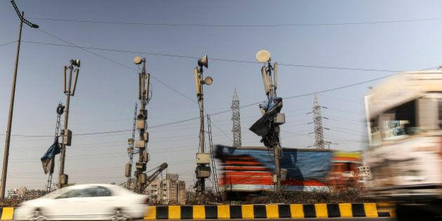 Traffic passes mobile phone telecommunications towers in Mumbai, India, on Wednesday, Jan. 29, 2014....