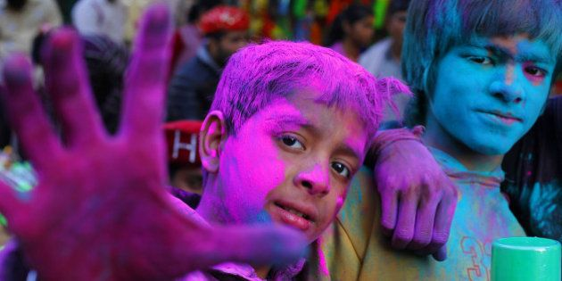 NEW DELHI, INDIA - MARCH 4: Indian children, smeared with gulal-coloured powder, smiles at the camera...
