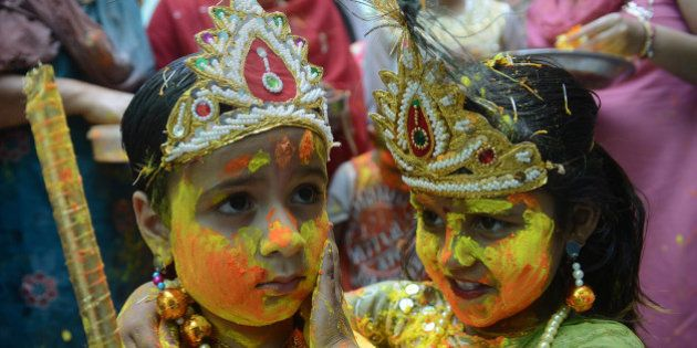 Indian children dressed as Lord Krishna (L) and Radha play with coloured powder during a Holi celebration...