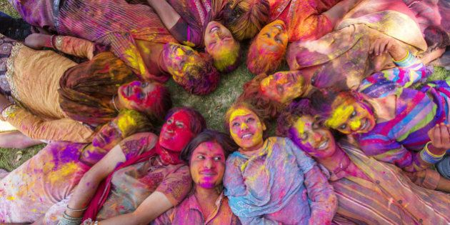 Young Indian people celebrating the Hindu festival of Holi by throwing coloured powder called Gulal at...